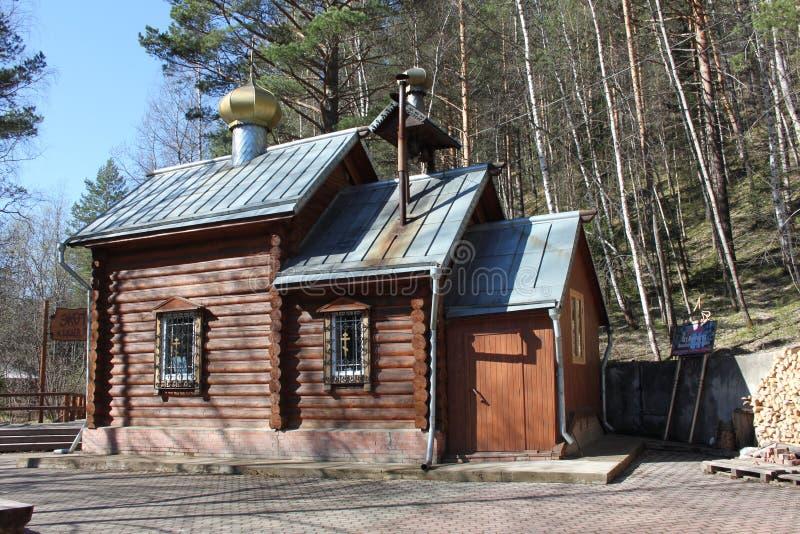 Uma igreja de madeira bonita com as abóbadas douradas na floresta no território da reserva nacional stolby de Krasnoyarskie fotos de stock royalty free