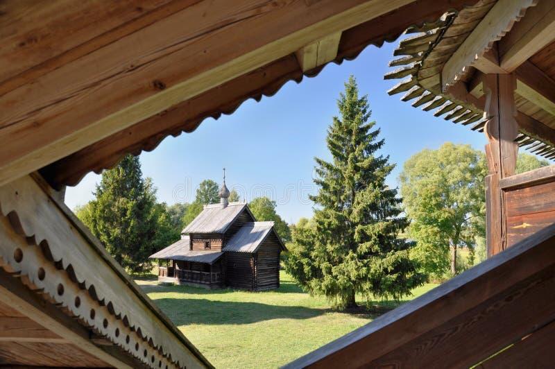 Uma igreja de madeira perto de uma árvore de abeto em Veliky Novgorod em um dia de verão, Rússia fotografia de stock royalty free