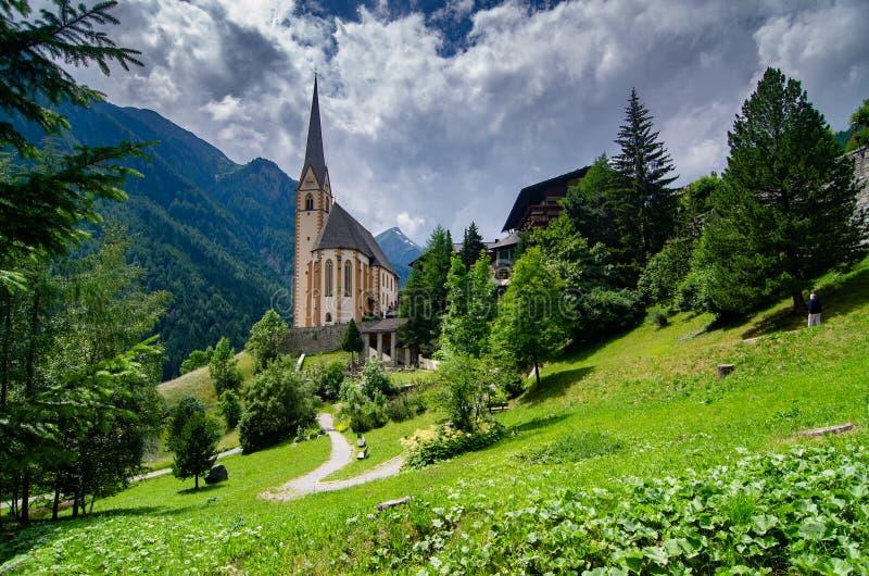 Uma igreja senta-se entre o terreno montanhoso em Heiligenblut, Áustria fotos de stock