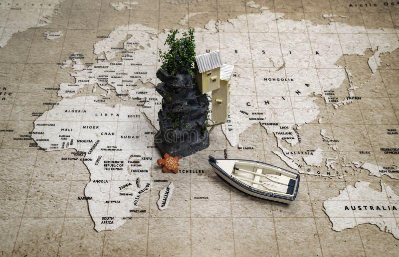 Uma ilha com casa e tartaruga com o barco de fileira no mapa do mundo imagens de stock
