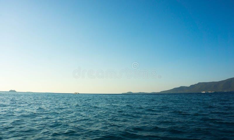 Uma ilha pequena para ver da distância com mar azul e o céu claro imagens de stock royalty free