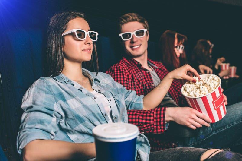 Uma imagem da empresa que senta-se junto em uma fileira no salão do cinema A menina está olhando o filme nos vidros e no alcance foto de stock