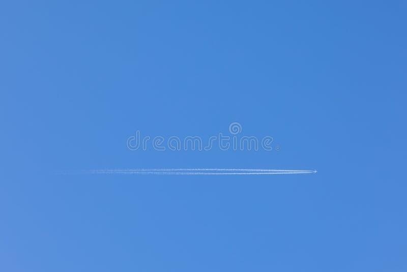 Uma imagem de alta resolução de um voo plano através do céu azul claro em cima, com uma fuga atrás dela Molde do modelo no fotografia de stock royalty free