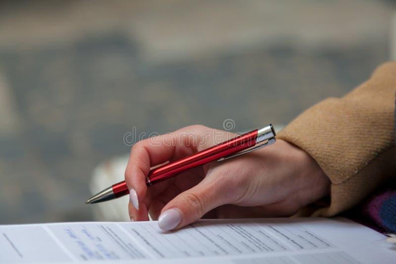 Uma imagem de uma mão e de uma pena que terminam um formulário fotografia de stock