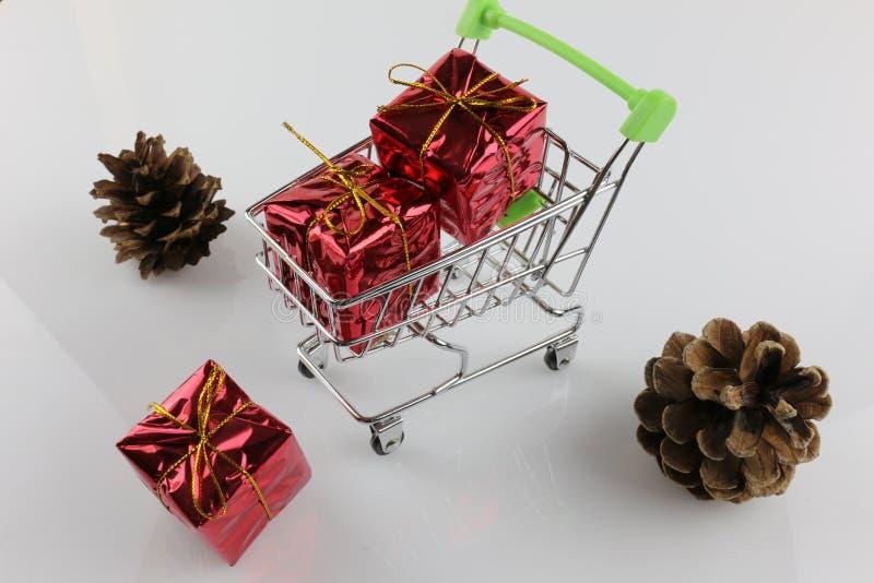 Uma imagem de um carrinho de compras com um presente - Natal do conceito fotografia de stock royalty free