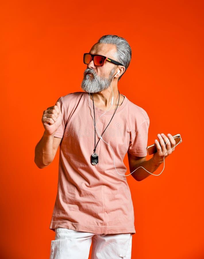 Uma imagem de um homem principal calvo idoso que escuta a m?sica com fones de ouvido imagem de stock royalty free