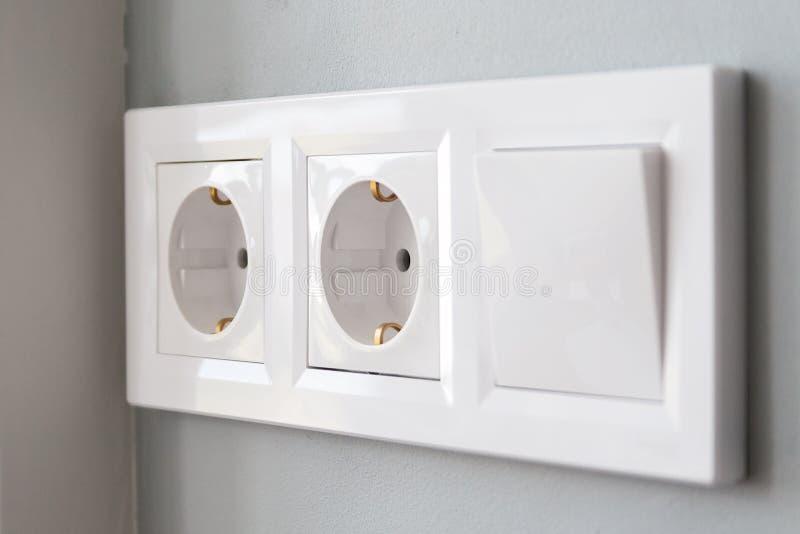 Uma imagem diagonal de proximidade de um grupo de tomadas elétricas europeias brancas e de um interruptor situado numa parede cin imagens de stock