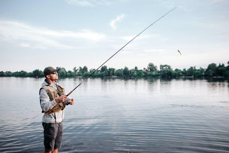 Uma imagem do fishaerman que está em raso e na pesca Guarda voa a haste O indivíduo olha acima e dianteiro É calmo fotos de stock royalty free