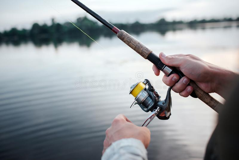 Uma imagem do girador rotative que o indivíduo sustente nas mãos Gerencie o carretel com mão esquerda Está no lago Está nivelando imagens de stock royalty free