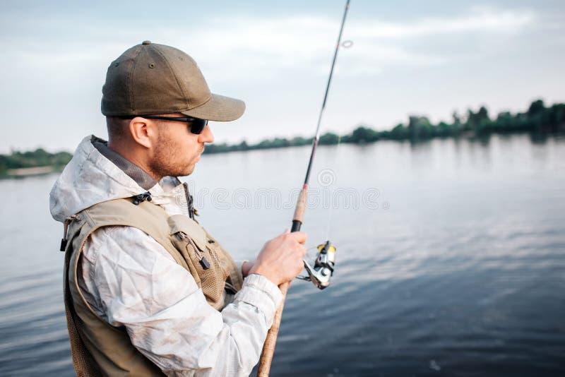 Uma imagem do homem no tampão, nos óculos de sol e na veste estando na haste de mosca rasa e olhando Está usando o carretel não-c fotografia de stock