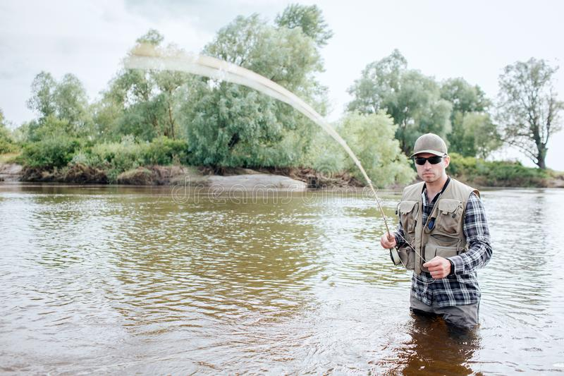 Uma imagem do homem que guarda a haste de mosca Está vibrando O indivíduo guarda a peça da colher na outra mão Está na água Ele imagens de stock
