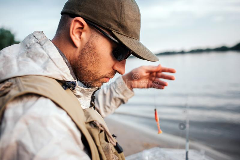 Uma imagem do homem que senta-se na borda da água e que olha para baixo Guarda a colher com isca O indivíduo está preparando-se à imagem de stock royalty free