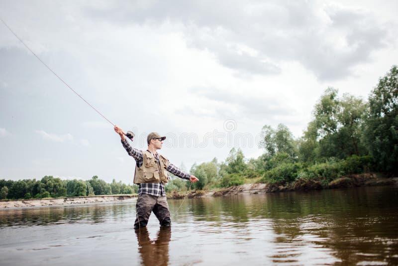 Uma imagem do homem que sustenta a haste de mosca no assistente Está estando na água pouco profunda e está olhando em linha reta  imagem de stock