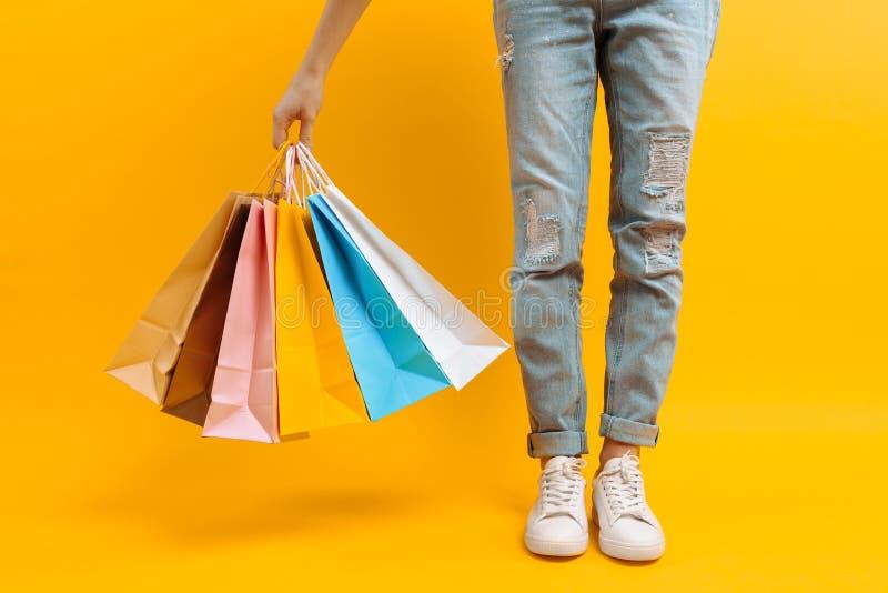 Uma imagem dos pés, uma mulher após suportes da compra com muitos sacos multi-coloridos, em um fundo amarelo imagens de stock