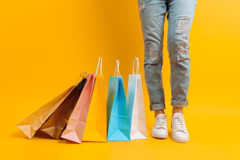 Uma imagem dos pés, uma mulher após suportes da compra com muitos sacos multi-coloridos, em um fundo amarelo fotografia de stock royalty free