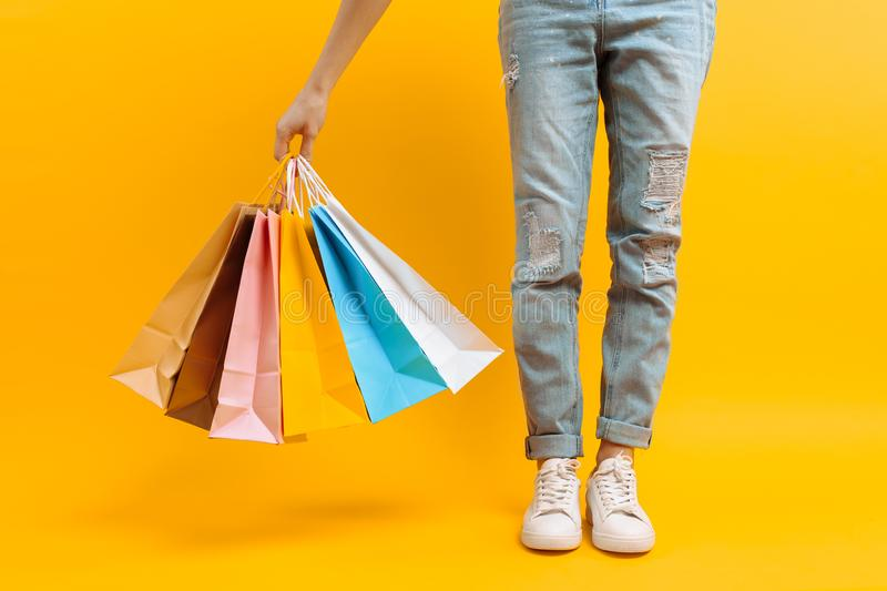 Uma imagem dos pés, uma mulher após suportes da compra com muitos sacos multi-coloridos, em um fundo amarelo imagem de stock royalty free