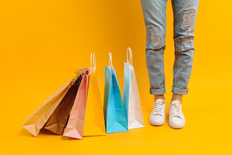 Uma imagem dos pés, uma mulher após suportes da compra com muitos sacos multi-coloridos, em um fundo amarelo foto de stock