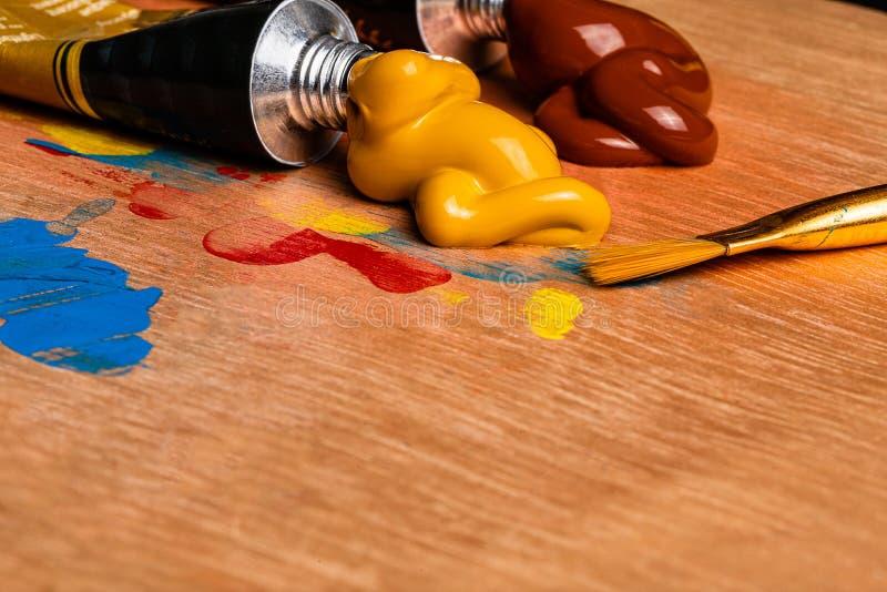 Uma imagem macro das pinturas acrílicas do artista espremeu em uma paleta de madeira para pintar fotos de stock
