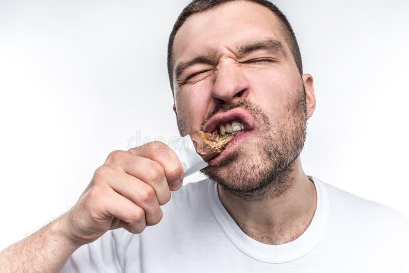 Uma imagem próxima do indivíduo que come a barra de chocolate doce com nouga Está mordendo uma parte grande deste doces O homem n fotografia de stock