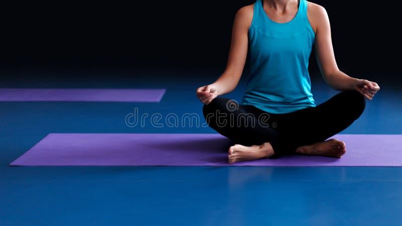 Uma ioga praticando da mulher em uma esteira imagem de stock royalty free