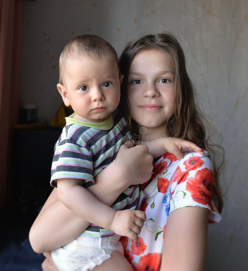 Uma irmã mais idosa guarda o irmão pequeno em seus braços imagem de stock royalty free