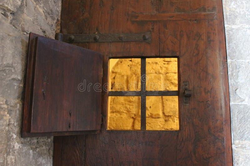 Uma janela aberta com grade do ferro de uma porta antiga de uma prisão ou de um Dungeon foto de stock