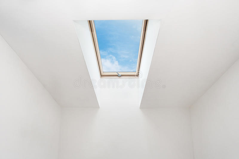 Uma janela aberta moderna da mansarda da claraboia em uma sala do sótão contra o céu azul fotografia de stock