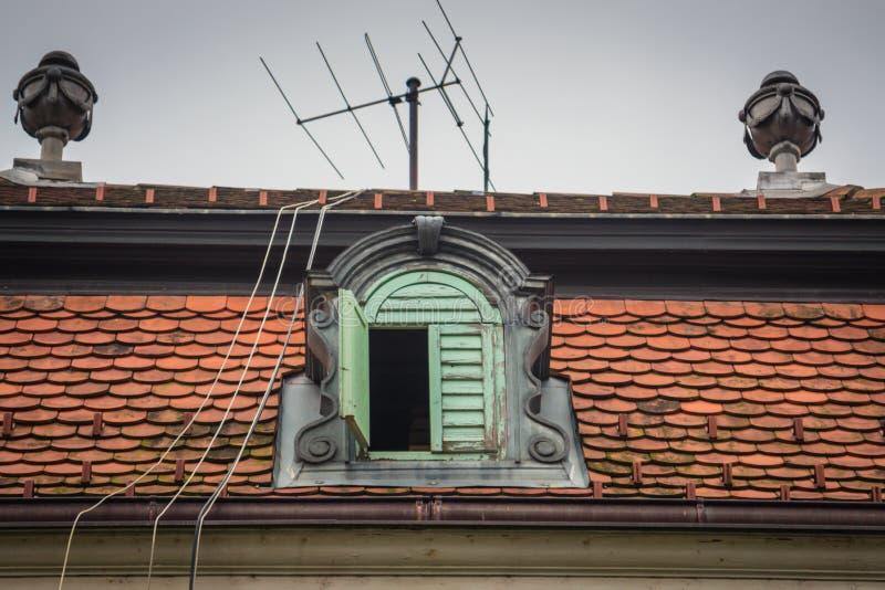 Uma janela do telhado da coroa com antena e fios foto de stock