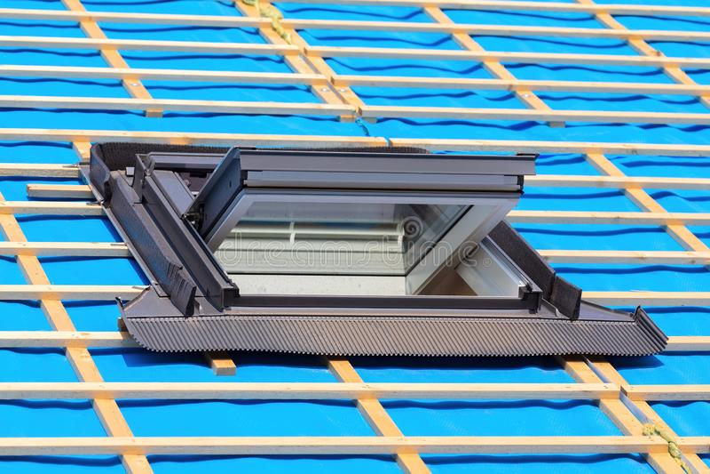 Uma janela do telhado no telhado de uma casa nova imagem de stock