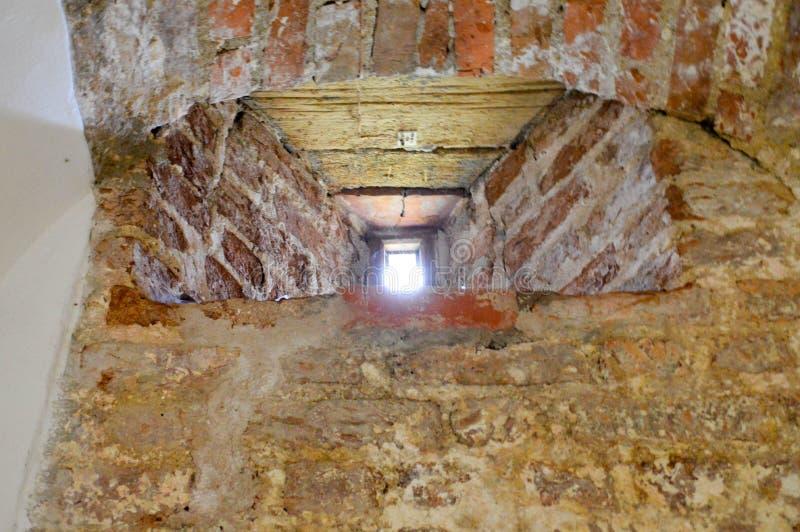 Uma janela estreita pequena em uma parede de tijolo gasto de pedra velha, antiga, rachada do tijolo vermelho no porão O fundo fotos de stock