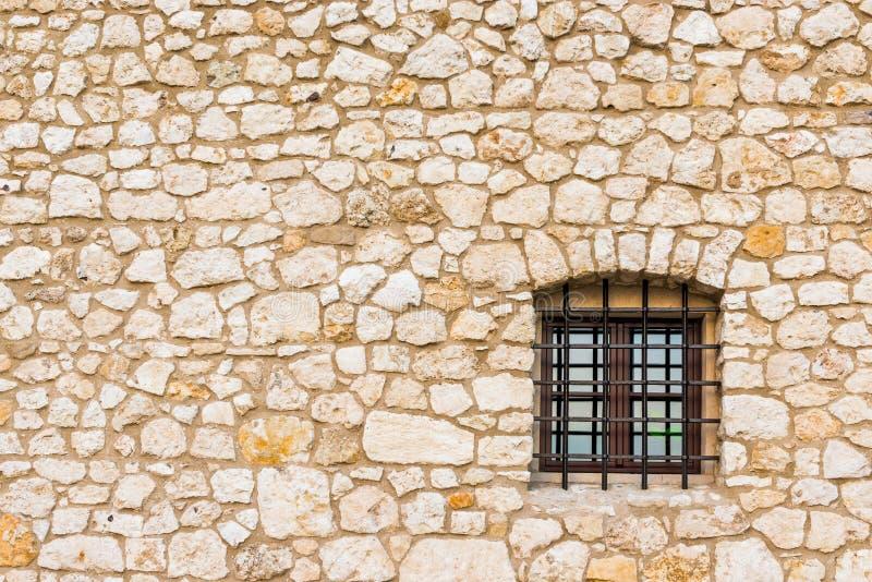 Uma janela pequena de um Dungeon com uma estrutura e de uma parede de pedra com imagens de stock