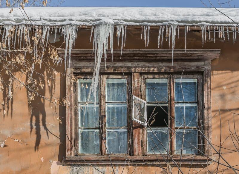 Uma janela velha com quadros marrons de madeira e um grupo de sincelos e neve e gelo transparente branco brilhante afiado e bordo imagem de stock