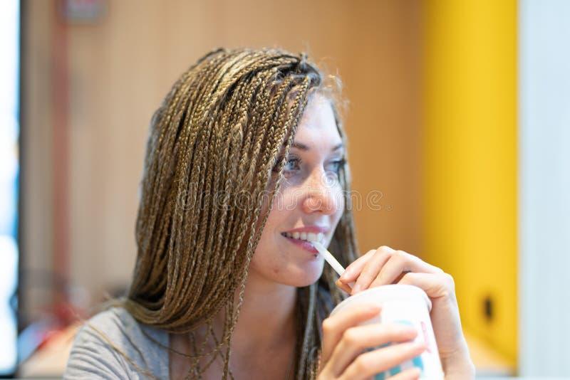 Uma jovem alegre sorridente bebendo uma bebida fotografia de stock royalty free