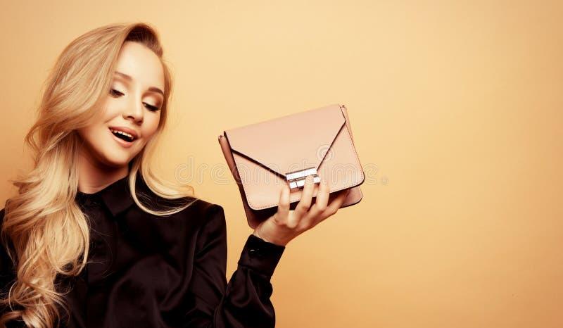 Uma jovem linda mulher numa blusa e calças castanhas segura uma bolsa e posando sobre um fundo bege fotografia de stock royalty free