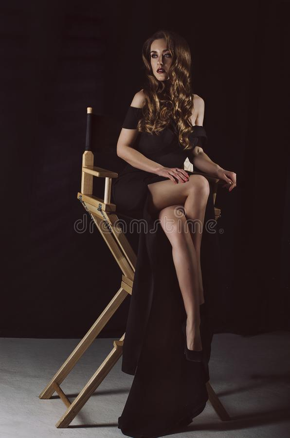 Uma jovem mulher à moda atrativa em um vestido preto longo senta-se em uma cadeira em uma sala escura Foto do estúdio Foto de Fas imagens de stock royalty free