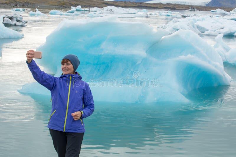 Uma jovem mulher é fotografada na perspectiva dos iceberg azuis Lagoa do gelo em Islândia imagem de stock