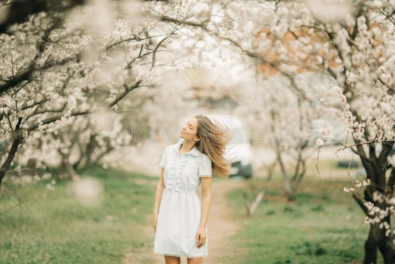 Uma jovem mulher anda entre o jardim de florescência foto de stock royalty free