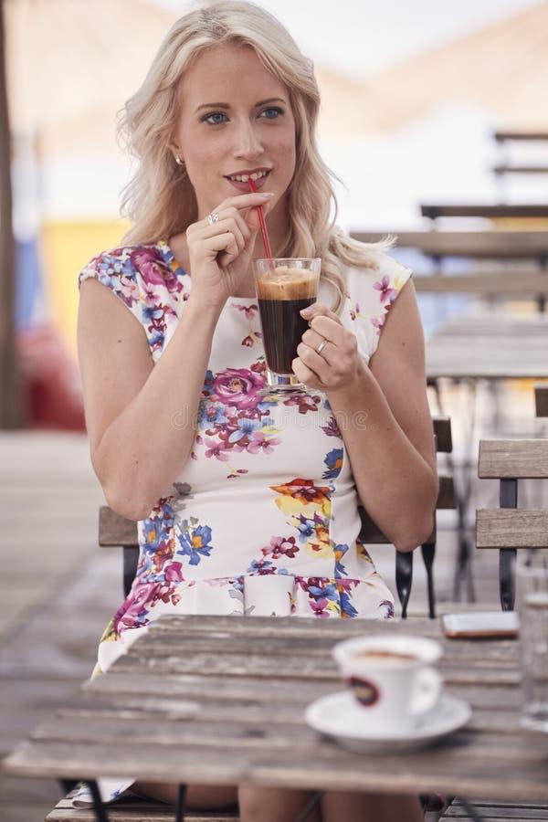 Uma jovem mulher, 25 anos velha, café bebendo, palha, sentando-se no café, tabelas de madeira, vista dianteira imagens de stock