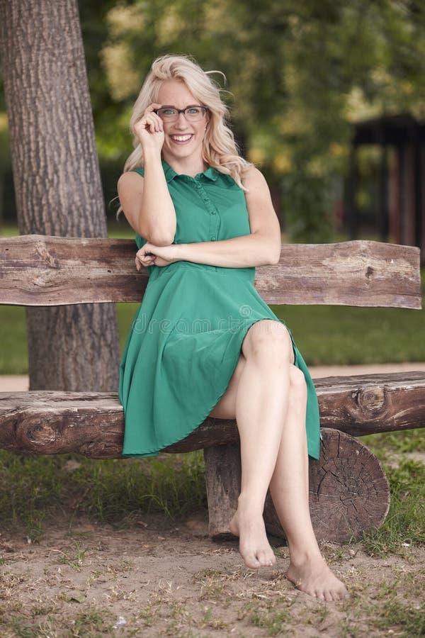 Uma jovem mulher, 25 anos velha, sentando-se no banco de madeira no parque, vestido verde, olhando à câmera tiro completo do comp fotos de stock royalty free