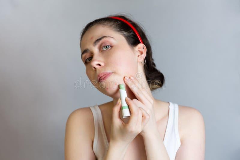 Uma jovem mulher bonita cobre seu queixo com um lápis do ocultador O conceito do controle da cosmetologia e da acne, adolescência imagem de stock royalty free