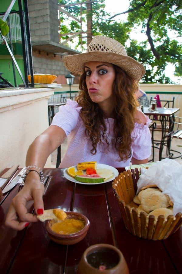 Uma jovem mulher bonita com alimento de oferecimento do chapéu para a câmera foto de stock royalty free