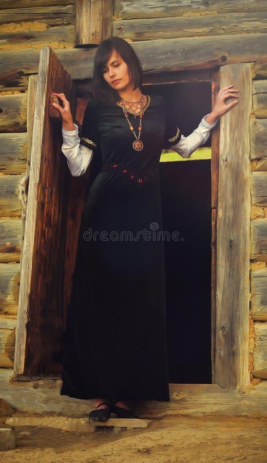 Uma jovem mulher bonita com cabelo escuro em um preto imagens de stock royalty free