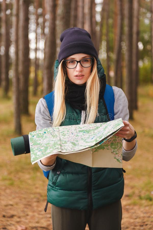 Uma jovem mulher bonita com mapa do curso e trouxa em plantações do pinho fotografia de stock royalty free