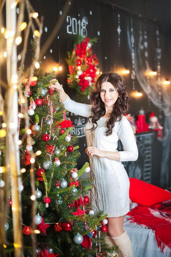 Uma jovem mulher bonita em um vestido da camiseta está decorando uma árvore de Natal Morena no quarto decorado para o Natal imagem de stock royalty free