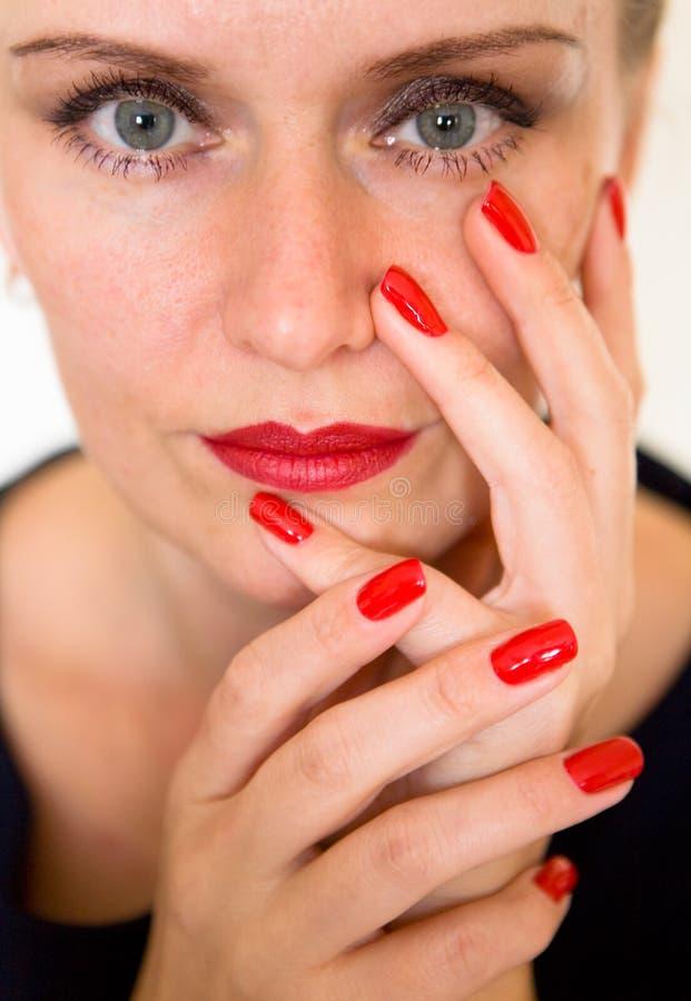 Uma jovem mulher bonita está tocando em sua cara com seus dedos imagem de stock