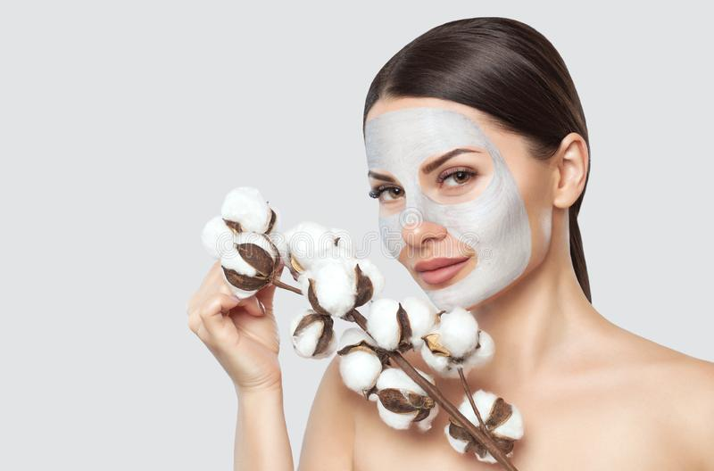 Uma jovem mulher bonita faz uma máscara hidratando em sua cara, ela está guardando uma flor do algodão em suas mãos imagens de stock royalty free