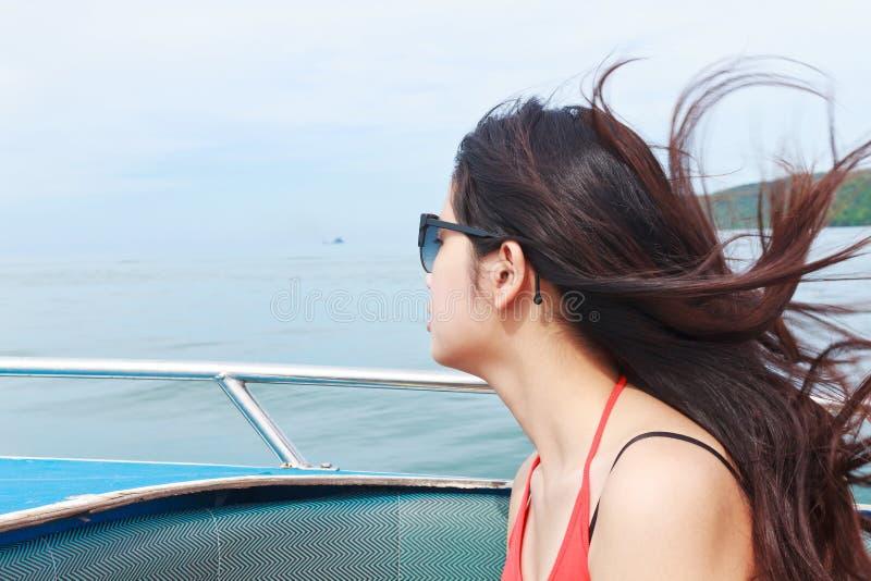 Uma jovem mulher bonita que relaxa no barco da velocidade imagens de stock