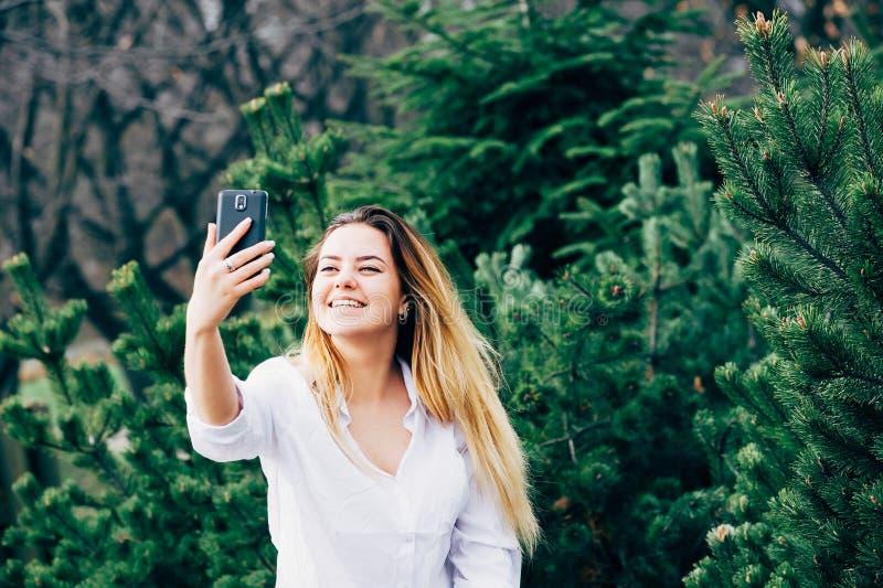 Uma jovem mulher bonita que sorri e que faz o selfie em um parque imagem de stock royalty free
