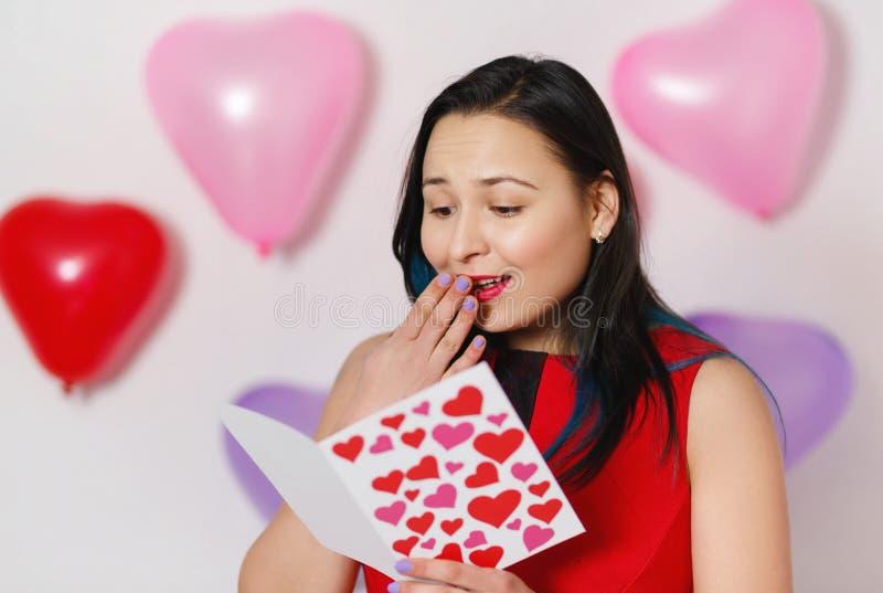Uma jovem mulher bonita toma um cartão com corações com uma declaração do amor Dia do `s do Valentim fotos de stock royalty free