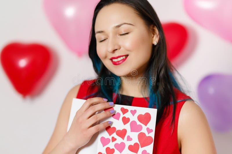 Uma jovem mulher bonita toma um cartão com corações com uma declaração do amor Dia do `s do Valentim fotos de stock